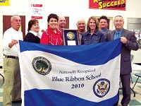 The CNE administration poses with a flag and plaque recognizing the Clermont Northeastern elementary school as a Blue Ribbon School.