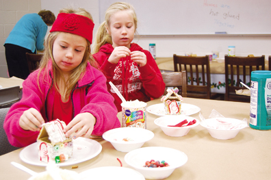 Ava Scanlan, left, and Laney Scanlan, create ginger bread houses at the Bethel branch of the Clermont County Library during Bethel Down Home Christmas Dec. 7.
