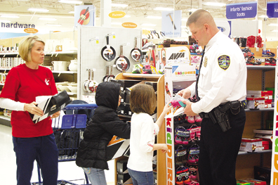 Union Township Police Officer Geremy Grooms helps children shop for clothing they need during the annual Shop with a Cop event.
