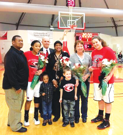 Ashley Keith, second from the left, and Stacie Lee, far right, pose with their families at the UC Clermont senior night celebration. The Lady Cougars would go on to win 77-71 over Kentucky Christian University.