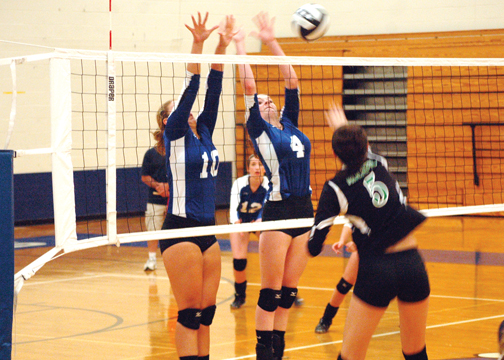 Junior right side hitter Samantha Ruehle, 10, and sophomore middle blocker Aubrey Young, 4, go up for a block during the Lady Wildcats' match against Fayetteville-Perry on Aug. 18.