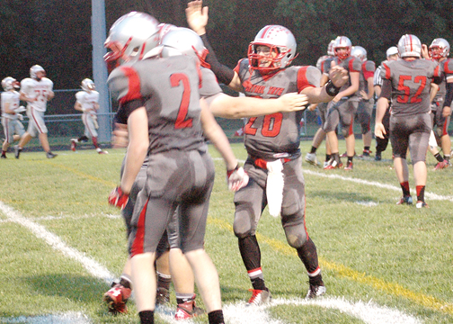 Jeffrey Botts, 26, and his teammates celebrate Botts' punt return touchdown in the second quarter of the Tigers' 28-16 win over Goshen on Friday, Sept. 12.