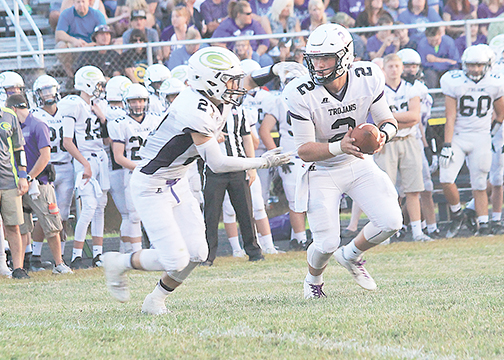Glen Este quarterback Tyler Pilcher hands off to Robby Boone during the Trojans' 60-23 win over Amelia on Aug. 28.