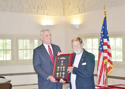 Congressman Brad Wenstrup, on left, presents medals to veteran James Arnold.