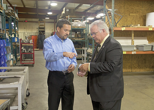 From left, Jason Dugle, president of Deltec in Batavia, shows Sen. Joe Uecker a part that the company manufactures during Uecker's visit to the business on Oct. 1, 2015.