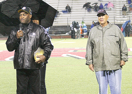New Richmond High School alumnus and former Pittsburgh Steeler Super Bowl champion, Dwayne Woodruff, left, addresses the crowd at New Richmond High School as Coach Ron Bird, right, looks on.