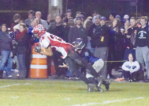 New Richmond's Corey Bozic dives in front of Amelia's wide receiver to make an interception late in the first half of New Richmond's 41-14 win on Oct. 14, 2016.