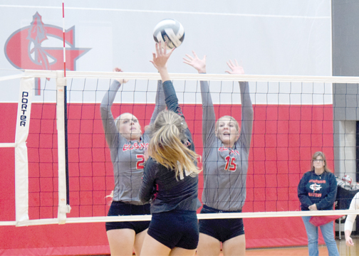Goshen's Melanie Jenkins (2) and Libby Umbarger (15) leap at the net in an attempt to block Colerain in the Lady Warriors' 3-0 win on Monday, Oct. 9, 2017.